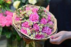 Kobieta trzyma bukiet róże zawijać w papierze zdjęcie stock