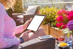 Kobieta trzyma cyfrową pastylkę w plenerowej kawiarni Fotografia Royalty Free