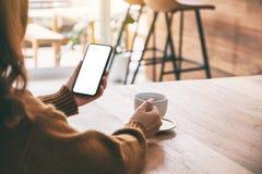 Kobieta trzyma czarnego telefon kom?rkowego z pustym ekranem podczas gdy pij?cy kaw? obraz royalty free