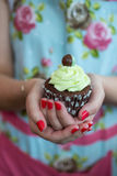 Kobieta trzyma czekoladowego cupca w Kwiecistej sukni z malującymi gwoździami Obraz Stock
