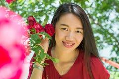 Kobieta trzyma czerwieni róży w czerwieni sukni Obrazy Royalty Free