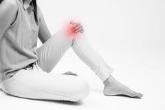Kobieta trzyma dalej bolesnego kolano na bielu fotografia stock