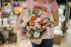 Kobieta trzyma eleganckiego kwiatu skład w złotym i różowym Obraz Royalty Free