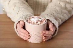 Kobieta trzyma filiżankę aromatyczny cacao z marshmallows na drewnianym stole w pulowerze obrazy stock