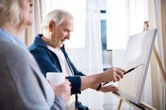 Kobieta trzyma filiżankę blisko uśmiechniętego mężczyzna obrazu obrazka na sztaludze Obrazy Stock