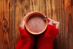 Kobieta trzyma filiżankę gorący cacao lub kawa na drewnianym tle, zbliżenie ręki w ciepłych czerwonych pulowerach Fotografia Royalty Free