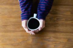 Kobieta trzyma filiżanki kawę jest rękami, odgórny widok, drewno zdjęcia stock