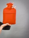 Kobieta trzyma gorącej wody butelkę w czerwonej runo pokrywie Zdjęcie Stock