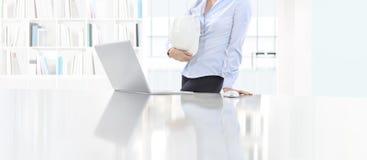 Kobieta trzyma hełm pracę przy biurkiem z komputerem w biurze, pr Fotografia Royalty Free