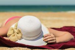 Kobieta trzyma jej kapelusz przeciw morzu Obrazy Royalty Free