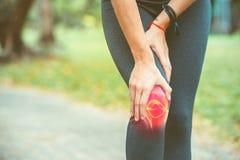 Kobieta trzyma jej kolano z czerwień bólem obraz royalty free