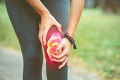 Kobieta trzyma jej kolano z czerwień bólem Sport opieka obrazy stock