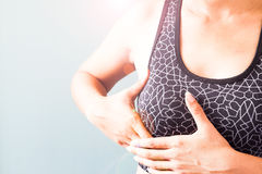 Kobieta trzyma jej pierś w sporta staniku, nowotwór piersi Obrazy Stock