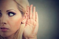 Kobieta trzyma jej rękę blisko ucho i słucha ostrożnie obrazy stock