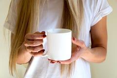 Kobieta trzyma kawowego kubek, projektująca akcyjna mockup fotografia Fotografia Stock
