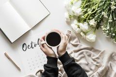 Kobieta trzyma kawowego kubek używać kalendarzowego minimalnego styl Obrazy Stock