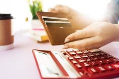 Kobieta trzyma kiesy, kredytowej karty w rękach i cyrklowania koszty Zdjęcia Stock