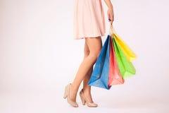 Kobieta trzyma kolorowych torba na zakupy w menchii sukni fotografia royalty free