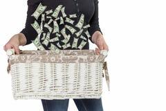 Kobieta trzyma koszykowy z spada dolarów amerykańskich rachunkami Obraz Stock