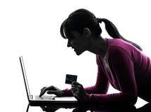 Kobieta trzyma kredytową kartę oblicza laptop fotografia stock
