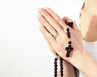 Kobieta trzyma krzyż z różana ono modli się i koralikami fotografia stock
