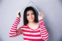 Kobieta trzyma laptop nad jej głowa jak dach Obraz Stock