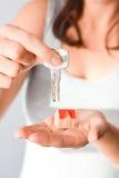 Kobieta trzyma małego modela dom, kluczowy proponowanie domu wynajem i nabycie lub fotografia stock