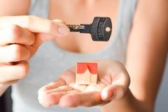 Kobieta trzyma małego modela dom, kluczowy proponowanie domu wynajem i nabycie lub Zdjęcie Royalty Free