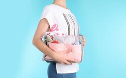 Kobieta trzyma macierzyńską torbę z dzieci akcesoriami na koloru tle obrazy royalty free