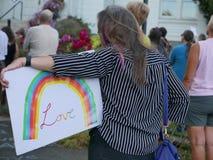 Kobieta trzyma ` miłości ` tęczy znaka przy politycznym wiecem Obrazy Stock