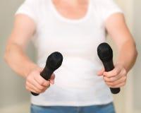 Kobieta trzyma mikrofony w jego rękach w białej koszula obrazy stock