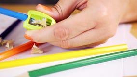 Kobieta trzyma ołówkową ostrzarkę i barwionego ołówek na drewnianym stole zbiory