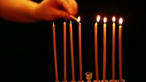 Kobieta trzyma płonącą świeczkę w jej ręce z którym zaświeca świeczki w candlestick dla Hanukkah Kobieta zaświeca świeczki zbiory