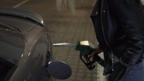 Kobieta trzyma paliwowego nozzle i refuel samochód w benzynowej staci przy nocą Boczny widok zbiory wideo