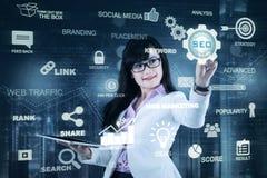 Kobieta trzyma pastylkę i naciskową SEO ikonę Obrazy Stock