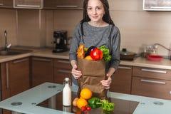 Kobieta trzyma pełną papierową torbę z produktami w rękach na tle kuchnia Zdrowa i świeża żywność organiczna zdjęcia royalty free