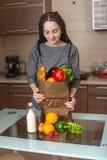Kobieta trzyma pełną papierową torbę z produktami w rękach na tle kuchnia Zdrowa i świeża żywność organiczna obrazy stock