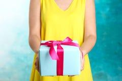 Kobieta trzyma pięknie zawijającego prezenta pudełko na koloru tle zdjęcia stock