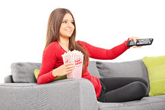 Kobieta trzyma pilot do tv i je popkorn Fotografia Stock