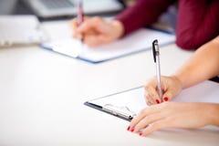 Kobieta trzyma pisać egzamin Zdjęcia Royalty Free