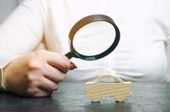 Kobieta trzyma powiększać - szkło nad miniaturowym drewnianym samochodem Obliczony koszt samochód Analiza i techniczna inspekcja obraz royalty free