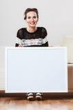 Kobieta trzyma pustej prezentaci deskę na kanapie Zdjęcia Royalty Free