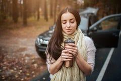 Kobieta trzyma rozporządzalną filiżankę kawy obok samochodu zamknięty zamknięta ręka jesień pojęcia odosobniony biel Jesieni laso zdjęcia royalty free