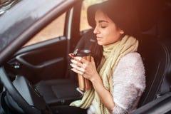 Kobieta trzyma rozporządzalną filiżankę kawy w samochodzie zdjęcie royalty free