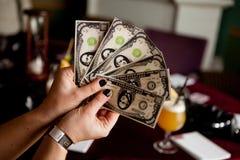 Kobieta trzyma rozszerzanie się sfałszowany pieniądze Obrazy Stock