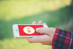 Kobieta trzyma smartphone wybiera numer przeciwawaryjną liczbę na ekranie g obrazy royalty free