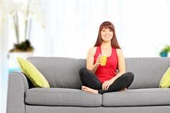 Kobieta trzyma sok pomarańczowego sadzający na kanapie indoors Zdjęcia Stock