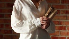 Kobieta trzyma starą książkę w białej koszula zdjęcie wideo