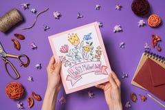 Kobieta trzyma szczęśliwego matka dzień pocztówkowy w rękach z dekoracjami wokoło na purpurach Zdjęcie Royalty Free