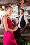 Kobieta trzyma szkło wino w ręce przy barem obraz royalty free
